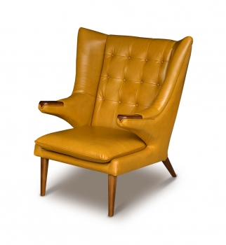 Leather armrest wing chair in leather tan brown with solid walnut wood application.