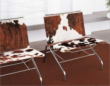 Amazing pony hide lounge chair with a stainless steel base. Cow skin brown white.
